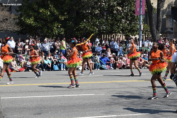 Young girl's dance team in orange at National Cherry Blossom Parade in Washington D.C.