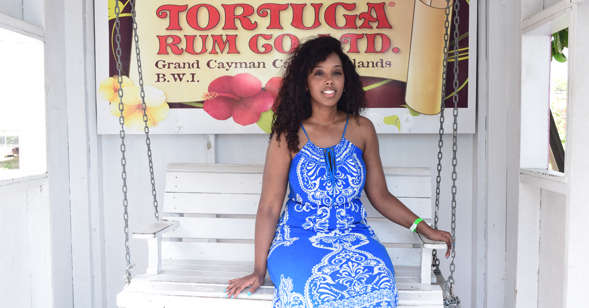 Travel Bloggers sit on white swinging chair at Tortuga Rum Co. LTD. in Grand Cayman