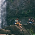 Black man and black woman sitting by a waterfall