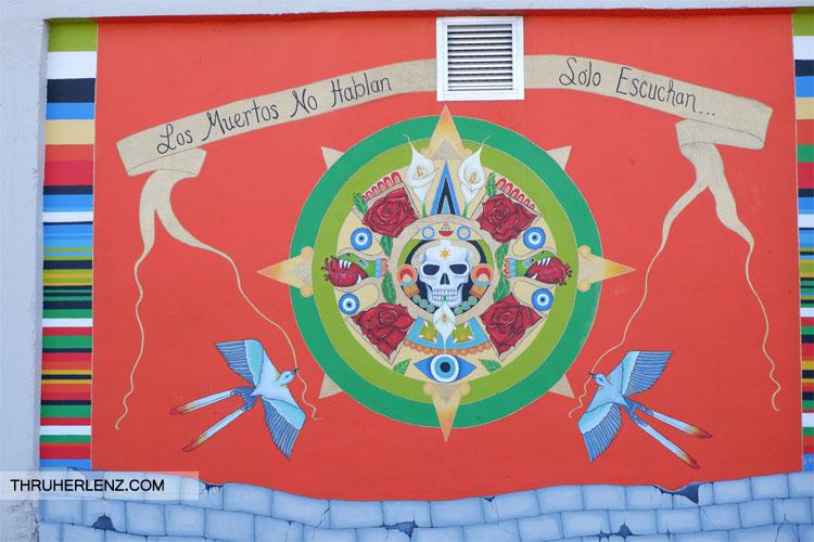 Skeleton head in circle with words los muertos no hablan solo escuchan with orange background