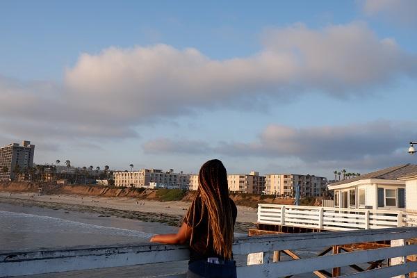 Girl at the boardwalk in San Diego overlooking Pacific Ocean