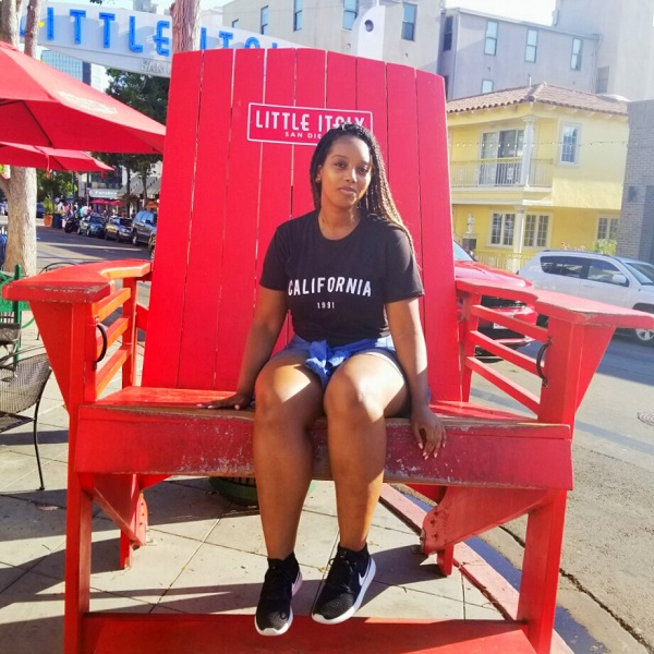 Woman sitting in big red chair in Little Italy San Diego