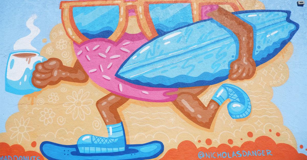 San Diego street mural of donut skateboarding with coffee