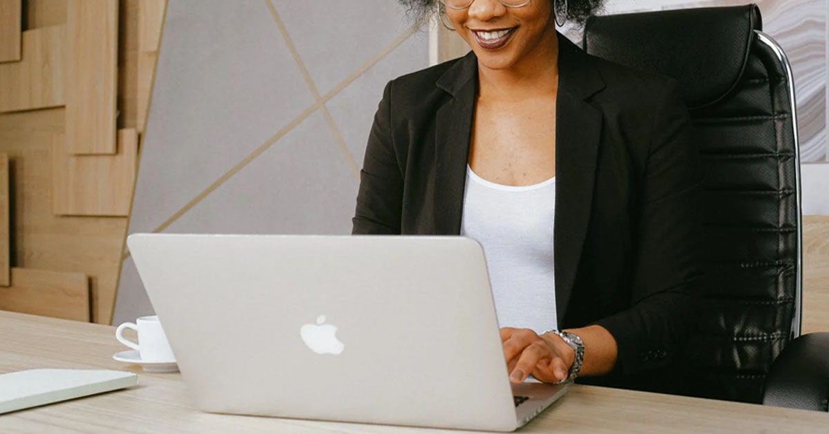 Woman typing on Mac computer at desk