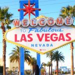 Black woman with locs in front of Las Vegas Nevada famous sign