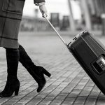 Stylish woman with suitcase and bag walking on street near modern airport terminal
